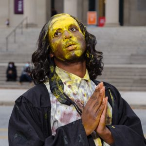 A black masc presenting person stands in front of the Baltimore Museum of Art in a black robe and a wavy dark brown wig. He stands drenched in yellow paint with his eyes looking upwards and his hands clasped in prayer.