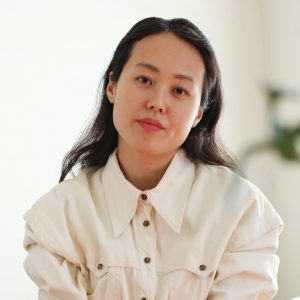A Korean person with black hair is wearing a cream button down top with brown quilted pants and is sitting in a chair with arms forward. There are tattoos that are visible on each arm. A plant and a corner of a table is visible in the foreground and in the background there is a beige couch.