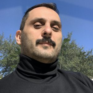 Georgian man with a mustache and dark hair in black turtleneck half-smiling looking into the camera under the bright sunlight on the background of light blue sky and green foliage.