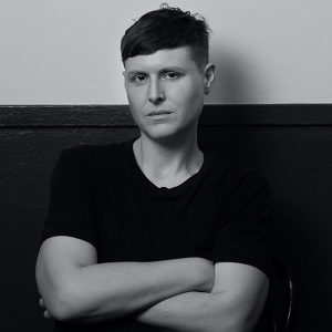 A white non-binary androgynous person with short hair in a black t-shirt stands in front of a wall with their arms crossed. The photograph is black and white.